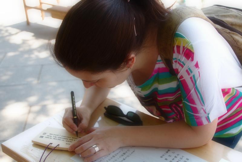 Lidia escribiendo en una tablilla ema el en Santuario Meiji de Harajuku en Tokio