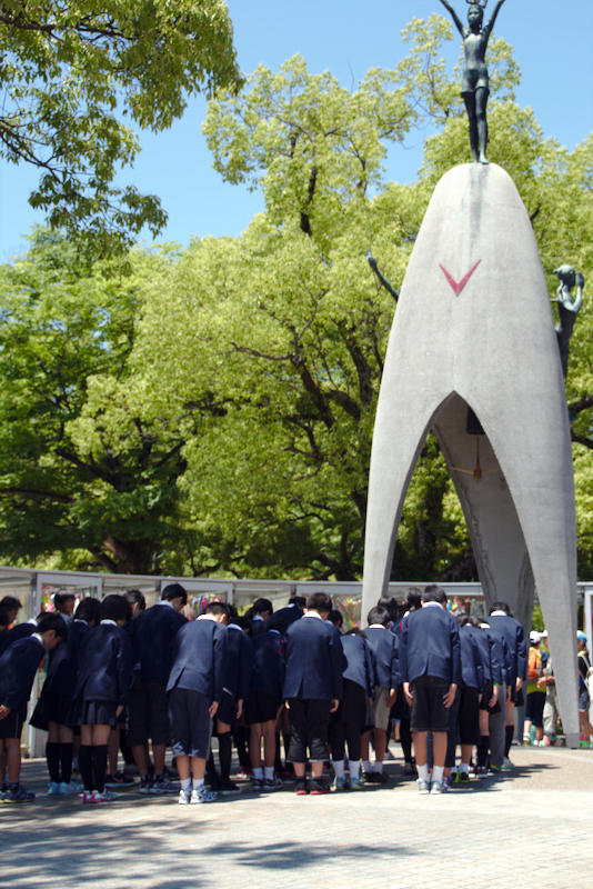 grupo de niños saludando delante del Monumento a la Paz de los niños en el Parque de la Paz de Hiroshima