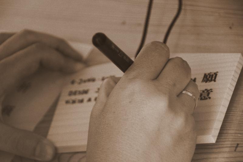escribiendo en una tablilla ema en el Santuario Meiji de Harajuku en Tokio